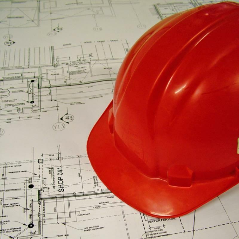 A construction hat resting on blueprints