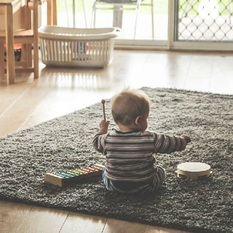 A baby playing with a xylophone