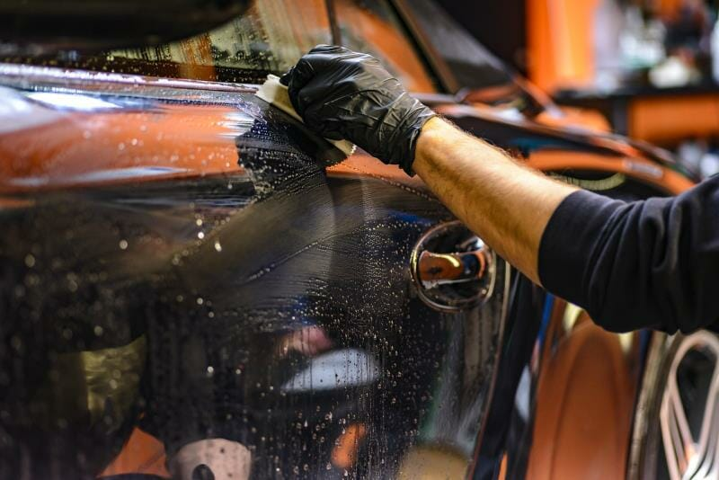 A person washing the exterior of a car